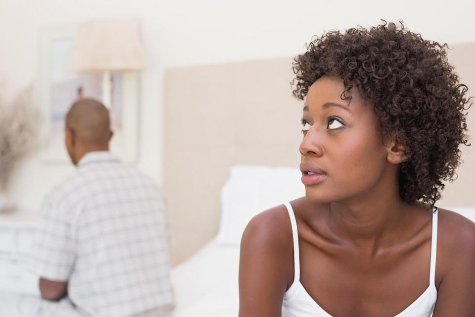 Unhappy couple not speaking to each other on bed at home in the bedroom