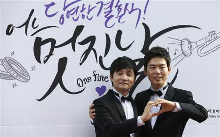 South Korean film director Kim Jho Gwang-soo (L) and his partner Kim Seung-hwan pose for media before their wedding ceremony in central Seoul September 7, 2013. REUTERS/Lee Jae-Won