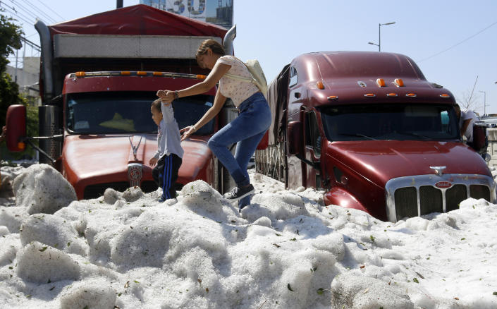 A woman and a child walk on hail in Guadalajara, Mexico, on June 30. (Photo: Ulisies Ruiz/AFP/Getty Images)