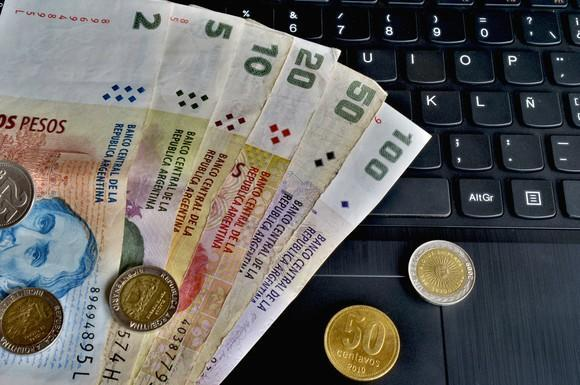 Argentine currency and coins on top of a black keyboard