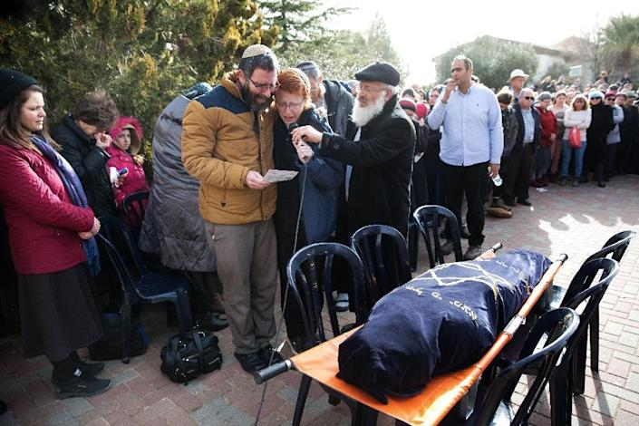 Natan, the husband of Dafna Meir, and her son speak during her funeral ceremony in the Jewish settlement of Otniel near the flashpoint city of Hebron in the southern West Bank on January 18, 2016 (AFP Photo/Menahem Kahana)
