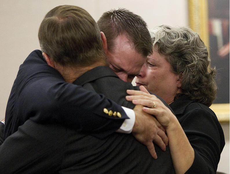 Former Houston police officer Andrew Blomberg, center, embraces his parents after he was found not guilty of official oppression in the videotaped beating of a 15-year-old burglary suspect, Wednesday, May 16, 2012 in Houston. Blomberg, 29, was the first of four fired police officers to stand trial for their roles in the alleged daylight beating of Chad Holley in March 2010. (AP Photo/Houston Chronicle, Brett Coomer) MANDATORY CREDIT-PHOTOGAPHER