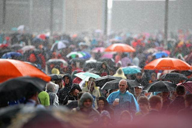LONDON, ENGLAND - JULY 29: Members of the public shelter from the rain at the Olympic Park on Day 2 of the London 2012 Olympic Games on July 29, 2012 in London, England. (Photo by Jeff J Mitchell/Getty Images)