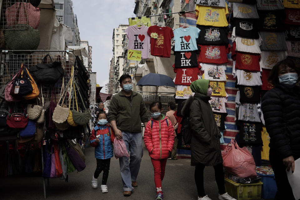 """People wear masks at a street where is selling tourist's souvenir in Hong Kong, Saturday, Feb, 1, 2020. China's death toll from a new virus continues to rise as a World Health Organization official says other governments need to prepare for""""domestic outbreak control"""" if the disease spreads. (AP Photo/Kin Cheung)"""