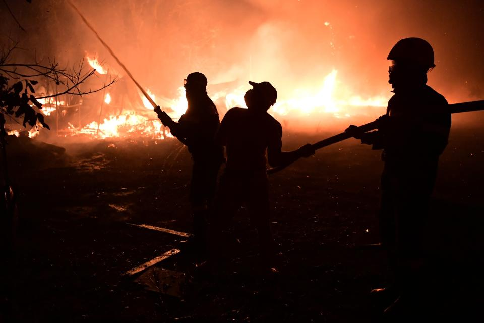 Firefighters and local residents try to extinguish the flames during a wildfire in Adames area, in northern Athens, Greece, Tuesday, Aug. 3, 2021.Thousands of people fled their homes north of Athens on Tuesday as a wildfire broke out of the forest and reached residential areas. The hurried evacuations took place just as Greece grappled with its worst heat wave in decades. (AP Photo/Michael Varaklas)