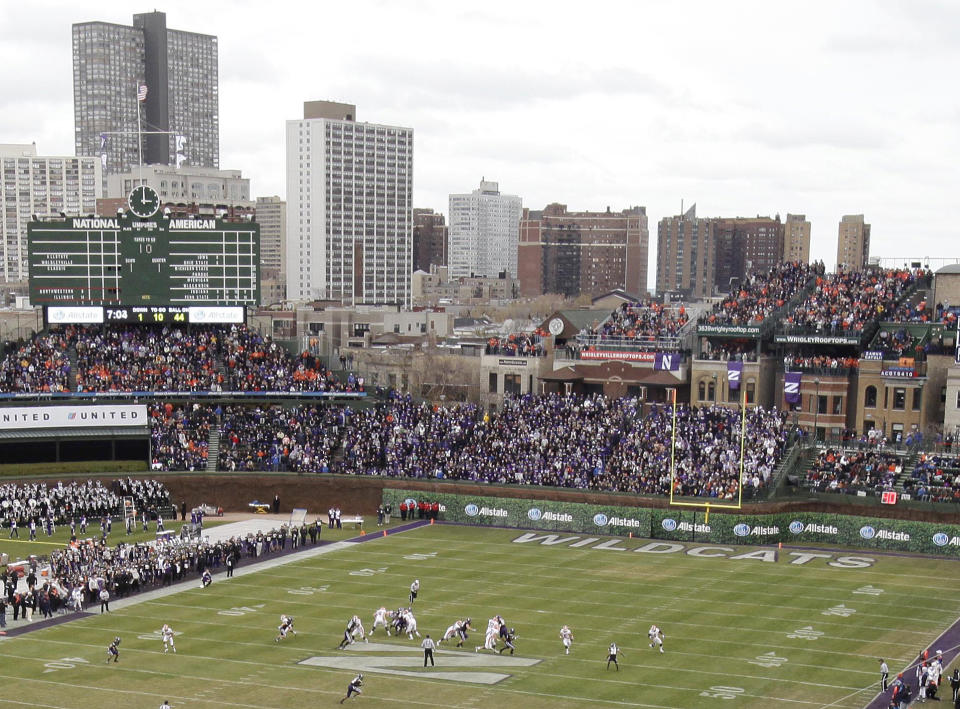 FILE - In this Nov. 20, 2010, file photo, Illinois' offense runs a play against Northwestern during the first quarter of an NCAA college football game at Wrigley Field, home of the Chicago Cubs basebal team, in Chicago. The day before Northwestern and Illinois played the first college football game at Wrigley Field in 72 years, the Big Ten decided the outfield wall was too close to the east end zone and that _ for the safety of the players _ all offensive plays would be run toward the west end zone. (AP Photo/Nam Y. Huh, File)