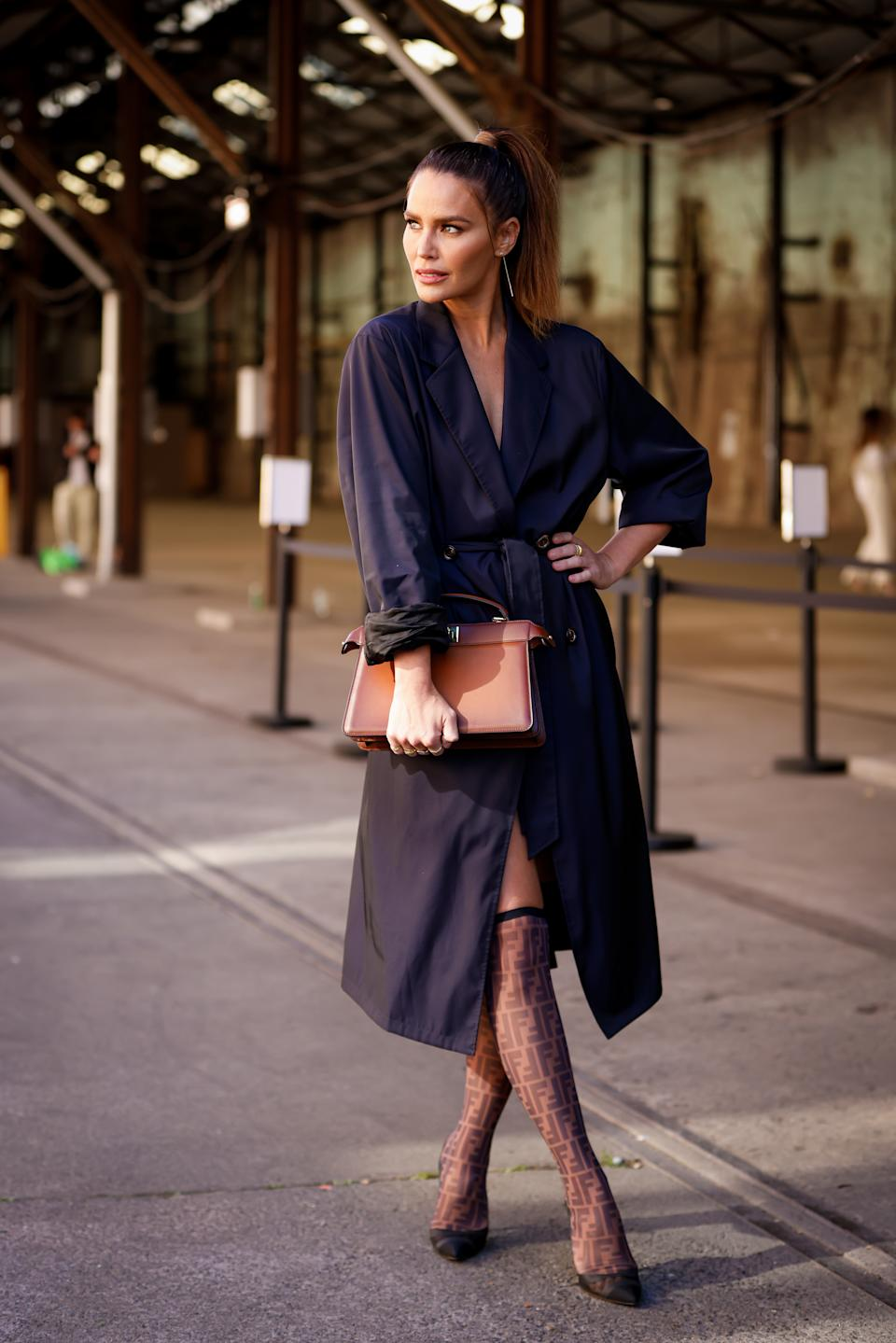 Jodi Gordon wearing Bally trench, Fendi bag, shoes and monogrammed stockings at Afterpay Australian Fashion Week 2021 on May 31, 2021 in Sydney, Australia