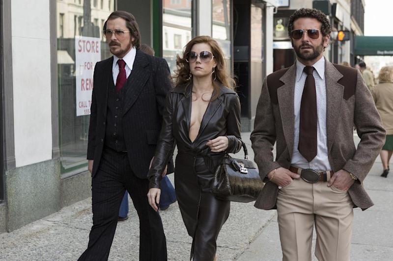 """In this photo released by Sony Pictures, Christian Bale, left, as Irving Rosenfeld, Amy Adams as Sydney Prosser, center, and Bradley Cooper as Richie Dimaso walk down Lexington Avenue in a scene from Columbia Pictures' film, """"American Hustle."""" Corruption tale """"American Hustle,"""" digital love story """"Her"""" and historic saga """"12 Years a Slave"""" are among the motion picture nominees for the Producers Guild of America announced Thursday, Jan. 2, 2014. (AP Photo/Sony - Columbia Pictures, Francois Duhamel)"""