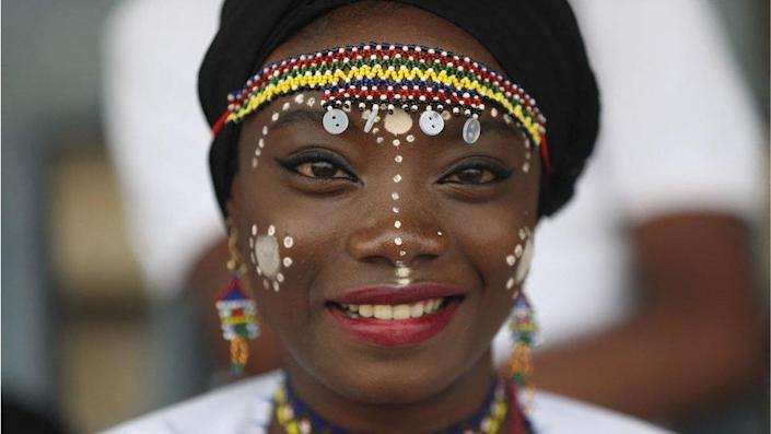 Member of acrobatic band smiling for a picture as Nigeria marked its 61st year of independence in Abuja. She is wearing intricate white face paint with dots down her nose, cheeks and around her eyebrows. She has on a multi-coloured beaded headband and is wearing red lipstick. She looks happy.