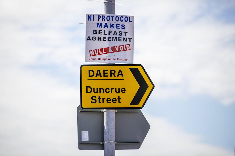 Anti NI Protocol sign above a sign for the Northern Ireland Department of Agriculture, Environment and Rural Affairs (DAERA) site on Duncrue Street in Belfast, which is one of the sites used when lorries roll off the ferries that is used to perform checks (Liam McBurney/PA) (PA Wire)