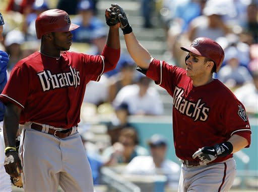 Arizona Diamondbacks Justin Upton, left, and Miguel Montero celebrate as both score on Montero's home run against the Los Angeles Dodgers in the eighth inning of a baseball game in Los Angeles, Wednesday, Aug. 1, 2012. (AP Photo/Reed Saxon)