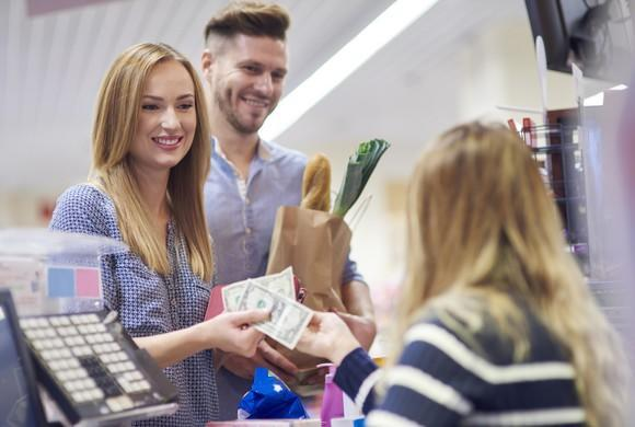 A woman and a man check into a grocery store and pay in cash.