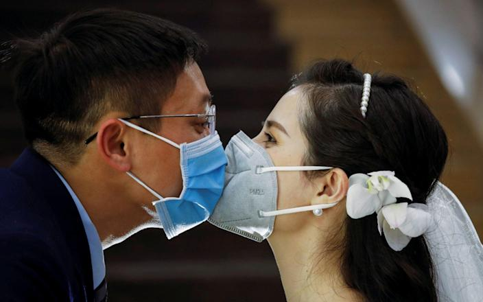 Vietnamese dentist Tran Phuong Thao and her husband Tran Minh Hieu kiss at their wedding ceremony in Hanoi - Reuters