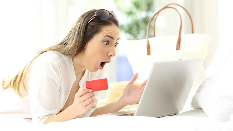Amazed woman looking surprised at her notebook computer screen, while holding a red card.
