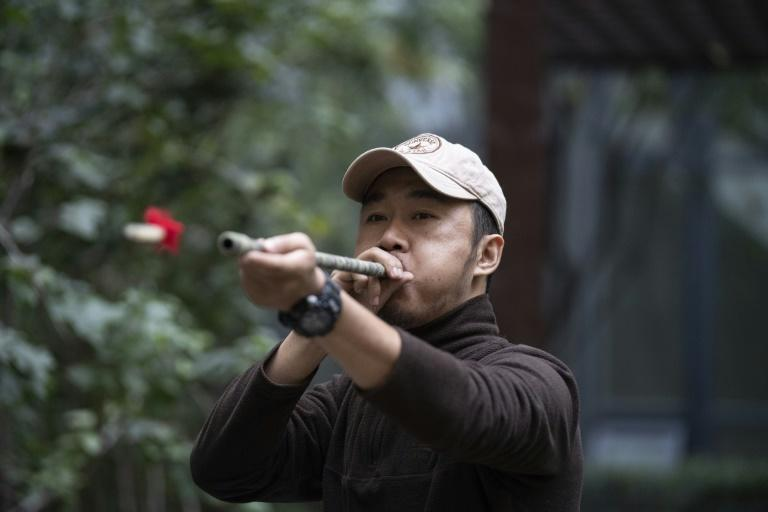 Chinese pet detective Sun Jinrong tests his blowdart as he prepares to search for a missing cat in a residential compound in Beijing (AFP Photo/NOEL CELIS)