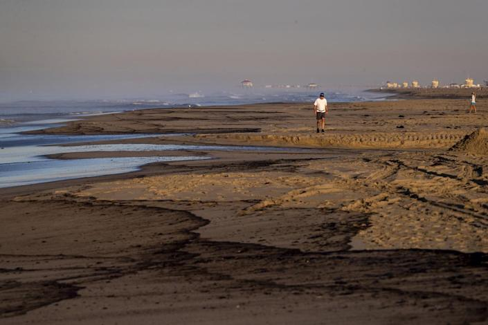 An oil slick lines the beach as a man walks, taking in the scene of a major oil spill washes ashore at Huntington State Beach