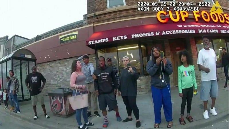 This May 25, 2020, file image from a police body camera shows bystanders including  Charles McMillan, center left in light colored shorts, Christopher Martin center in gray, Donald Williams, center in black, Genevieve Hansen, fourth from right filming, Darnella Frazier, third from right filming, as former Minneapolis police officer Derek Chauvin was recorded pressing his knee on George Floyd's neck for several minutes in Minneapolis.