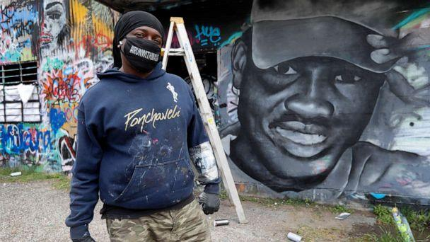 PHOTO: Artist Theo Ponchaveli wears a mask he created that reads, 'Runwithmaud', as he poses for a photo in front of a mural that he is painting in the likeness of Ahmaud Arbery in Dallas, Friday, May 8, 2020. (Tony Gutierrez/AP)