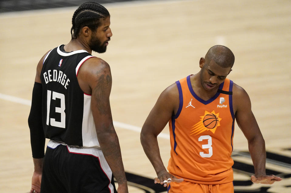 Los Angeles Clippers guard Paul George, left, tires to talk to Phoenix Suns guard Chris Paul during the second half in Game 3 of the NBA basketball Western Conference Finals Thursday, June 24, 2021, in Los Angeles. (AP Photo/Mark J. Terrill)