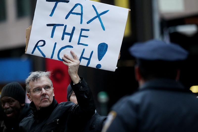 """NEW YORK, NY - MARCH 24:  A protester holds a """"Tax the Rich"""" sign as he marches during a rally against budget slashing held by union supporters on March 24, 2011 in New York City. The protesters called for closing tax loopholes for the wealthy and ending budget cuts for social programs. (Photo by Mario Tama/Getty Images)"""