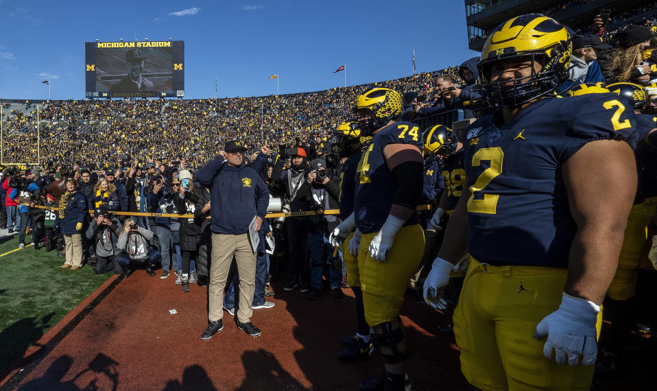 Michigan head coach Jim Harbaugh, center, prepares to lead his team on to the Michigan Stadium field before an NCAA college football game against Michigan State in Ann Arbor, Mich., Saturday, Nov. 16, 2019. (AP Photo/Tony Ding)