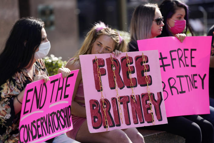 Alandria Brown, second from left, of Hendersonville, Tenn., sits with William Henry of Los Angeles, far left, and other Britney Spears supporters outside a court hearing concerning the pop singer's conservatorship at the Stanley Mosk Courhouse, Thursday, Feb. 11, 2021, in Los Angeles. (AP Photo/Chris Pizzello)