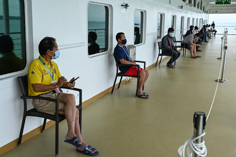 Migrant workers wearing face masks sit on socially distanced seats onboard the SuperStar Gemini cruise ship, currently used to accommodate foreign workers who have recovered from the COVID-19 novel coronavirus, at the Marina Bay Cruise Centre terminal in Singapore on May 23, 2020. (Photo by Roslan RAHMAN / AFP) (Photo by ROSLAN RAHMAN/AFP via Getty Images)