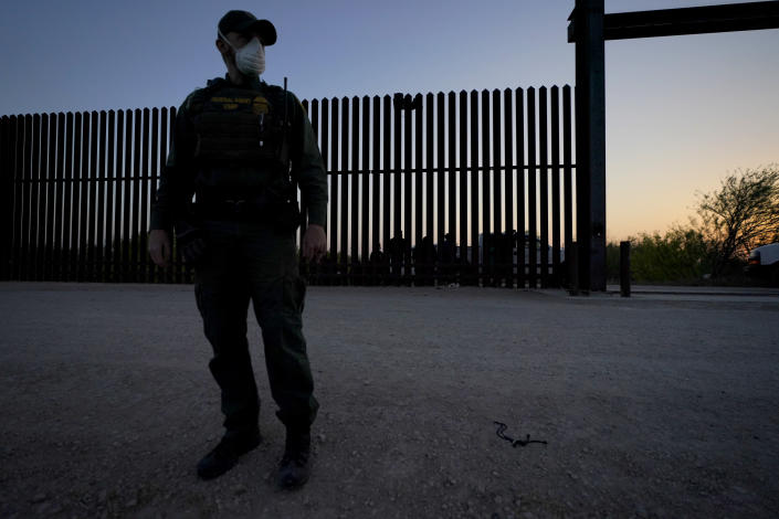 """A U.S. Customs and Border Protection agent looks on near a gate on the U.S.-Mexico border wall as agents take migrants into custody, Sunday, March 21, 2021, in Abram-Perezville, Texas. The fate of thousands of migrant families who have recently arrived at the Mexico border is being decided by a mysterious new system under President Joe Biden. U.S. authorities are releasing migrants with """"acute vulnerabilities"""" and allowing them to pursue asylum. But it's not clear why some are considered vulnerable and not others. (AP Photo/Julio Cortez)"""