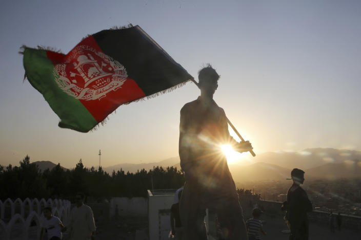 FILE - In this Aug. 19, 2019, file photo, a man waves the Afghan national flag during Independence Day celebrations in Kabul, Afghanistan. The U.N. mission in Afghanistan report released on Monday, July 27, 2020, has noted a drop in the number of civilians killed in violence in the first six months of this year, compared to the same period last year. (AP Photo/Rafiq Maqbool, File)