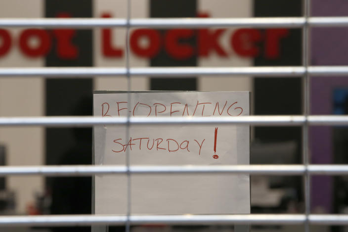 A sign advises shoppers that the Foot Locker store at the Yuba Sutter Mall will not open for a few more days, in Yuba City, Calif., Wednesday, May 6, 2020. Several dozen shoppers streamed into the first California mall to reopen Wednesday, despite Gov. Gavin Newsom's orders restraining businesses because of the coronavirus pandemic. (AP Photo/Rich Pedroncelli)
