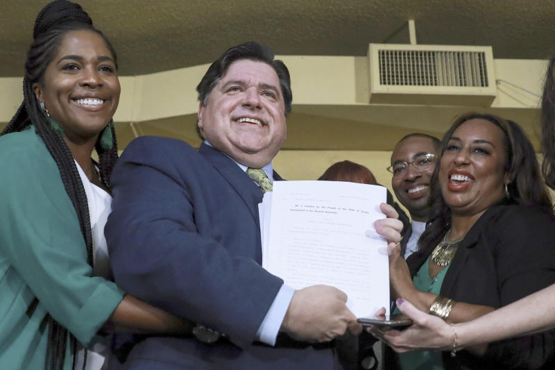 FILE - In this June 25, 2019 file photo, Gov. J. B. Pritzker holds a bill that legalizes adult-use cannabis in the state of Illinois accompanied by state Rep. Kelly Cassidy, left, and state Sen. Toi Hutchinson, right, in Chicago. Illinois becomes the 11th to legalize the adult-use of recreational marijuana. Like in other states before it, advocates of legalizing recreational marijuana use in Illinois want the law to look backward as well as forward. It conscientiously attempts to ensure that those who profit from growing and selling the weed have substantial representation from the mostly impoverished neighborhoods nailed the hardest by decades of drug crackdowns. (AP Photo/Amr Alfiky File)