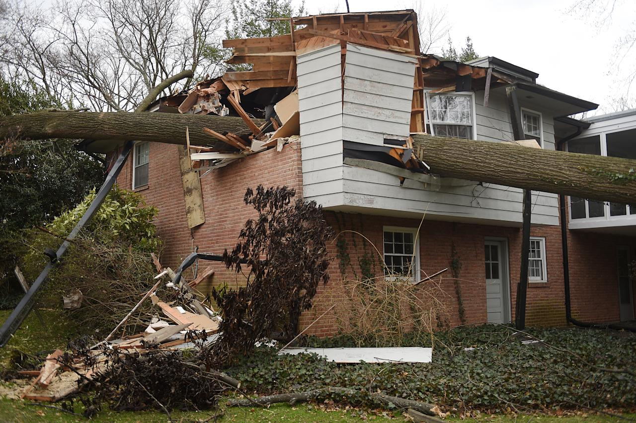 <p>A large tree fell on a house of a 100-year-old woman in Kensington, Md., while a powerful storm generated significant high winds on March 2, 2018, causing wide-spread flooding and trees to topple around the region. The woman was rescued and survived the accident. (Photo: Astrid Riecken for The Washington Post via Getty Images) </p>