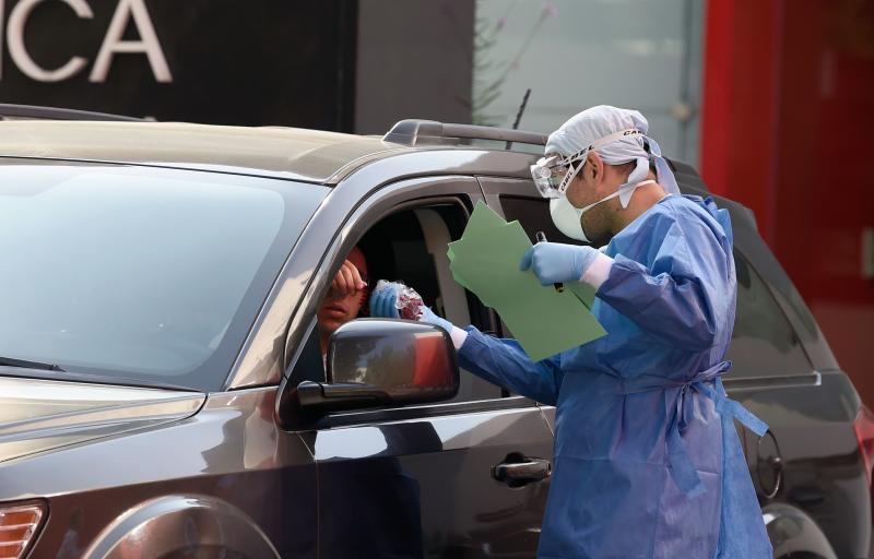 """A doctor hands documents to a person on a car as a questionnaire is done before the COVID-19 test at the Biomedica Lab in Mexico City on March 30, 2020. - Mexico's undersecretary of health prevention and promotion, Hugo Lopez-Gatell Ramirez, said the country was entering """"phase two"""" of its coronavirus approach, moving from containment to """"mitigation."""" (Photo by ALFREDO ESTRELLA / AFP) (Photo by ALFREDO ESTRELLA/AFP via Getty Images)"""
