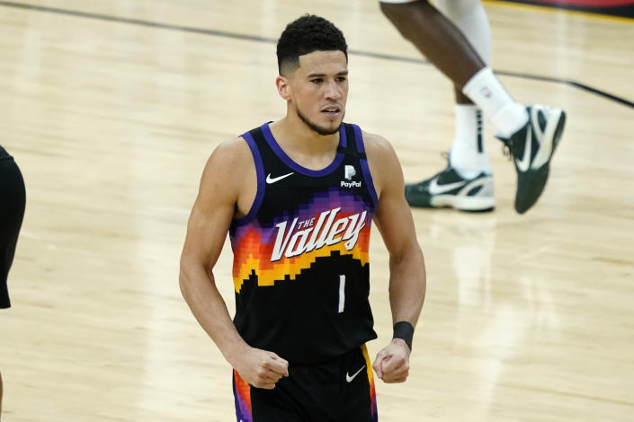 Phoenix Suns guard Devin Booker (1) pumps his fists after a basket against the Milwaukee Bucks during the second half of Game 1 of basketball's NBA Finals, Tuesday, July 6, 2021, in Phoenix. (AP Photo/Matt York)