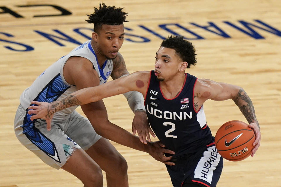 Connecticut's James Bouknight drives past Creighton's Antwann Jones during the first half of an NCAA college basketball game in the semifinals in the Big East men's tournament Friday, March 12, 2021, in New York. (AP Photo/Frank Franklin II)