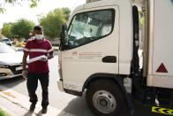 In this Tuesday, April 7, 2020 photo, a delivery man leaves after dropping off alcohol at a home in Dubai, United Arab Emirates. Dubai's two major alcohol distributors have partnered to offer home delivery of beer, spirits and wine as the new coronavirus now threatens a crucial source of tax and general revenue for the rulers of this Islamic city-state. The decision marks yet another loosening of social mores in the skyscraper-studded desert metropolis. (AP Photo/Jon Gambrell)