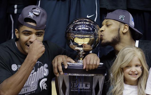 Michigan State's Gary Harris, left, poses with the championship trophy as Adreian Payne kisses it after they defeated Michigan 69-55 in an NCAA college basketball game in the championship of the Big Ten Conference tournament on Sunday, March 16, 2014, in Indianapolis. Lacey Holsworth, lower right, who is battling cancer and has become close to Payne, looks on. (AP Photo/Michael Conroy)