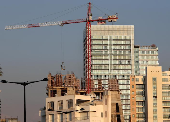 In this February 18, 2014 photo, a construction worker is carried in a basket by a crane, as he works on a luxury tower, in Beirut, Lebanon. Beirut is no different than Dubai, Doha or other major world cities overtaken by a global trend for modern, tall buildings. But in a country that prides itself on its rich history, many complain that Lebanon is losing its charm and character, often said to be the only thing going for it. (AP Photo/Hussein Malla)