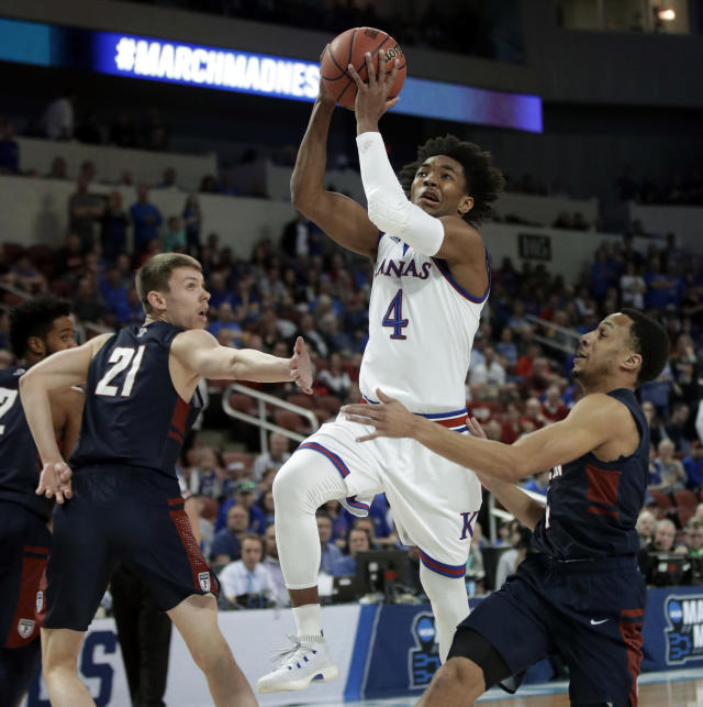 Kansas guard Devonte' Graham (4) splits Pennsylvania defenders Ryan Betley (21) and Darnell Foreman, right, during the first half of an NCAA college basketball tournament first-round game, Thursday, March 15, 2018, in Wichita, Kan. (AP Photo/Orlin Wagner)