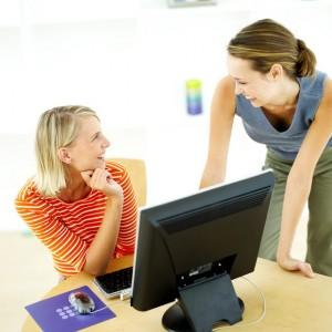 Laughing secretaries in front of computer