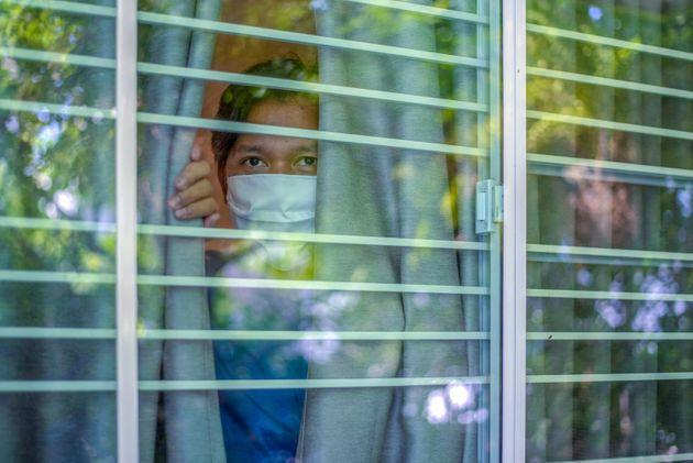 Man wearing a protective mask is looking out of the window. Home quarantine for 14 days due to the coronavirus COVID-19 epidemic. (Photo: athima  tongloom via Getty Images)