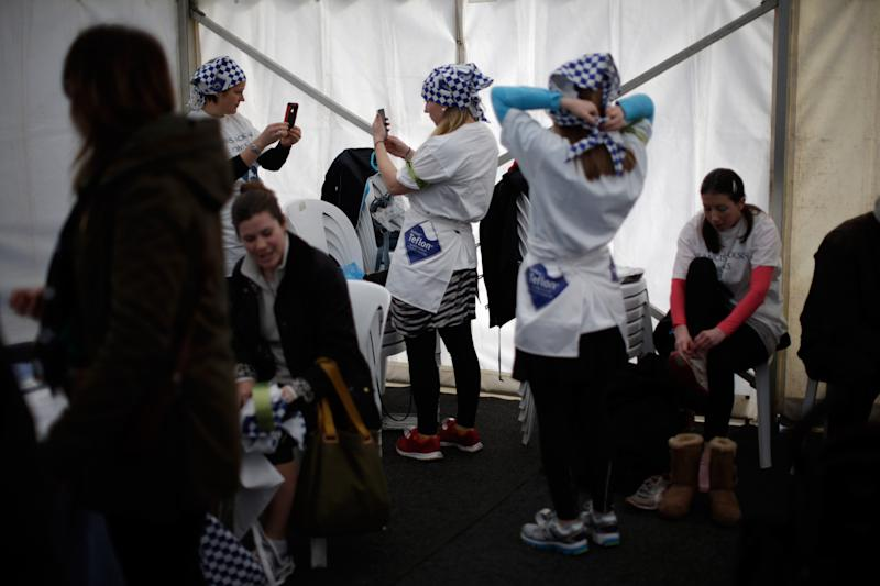 Participants get ready before the start of the annual Shrove Tuesday trans-Atlantic pancake race, in the town of Olney, in Buckinghamshire, England, Tuesday, March 4, 2014. Every year women clad in aprons and head scarves from Olney and the city of Liberal, in Kansas, USA, run their respective legs of the race with a pancake in their pan, flipping it at the beginning and end of the race. According to legend, the Olney race started in 1445 when a harried housewife arrived at church on Shrove Tuesday still clutching her frying pan with a pancake in it. Liberal challenged Olney to a friendly international competition in 1950 after seeing photos of the race in a magazine. (AP Photo/Matt Dunham)