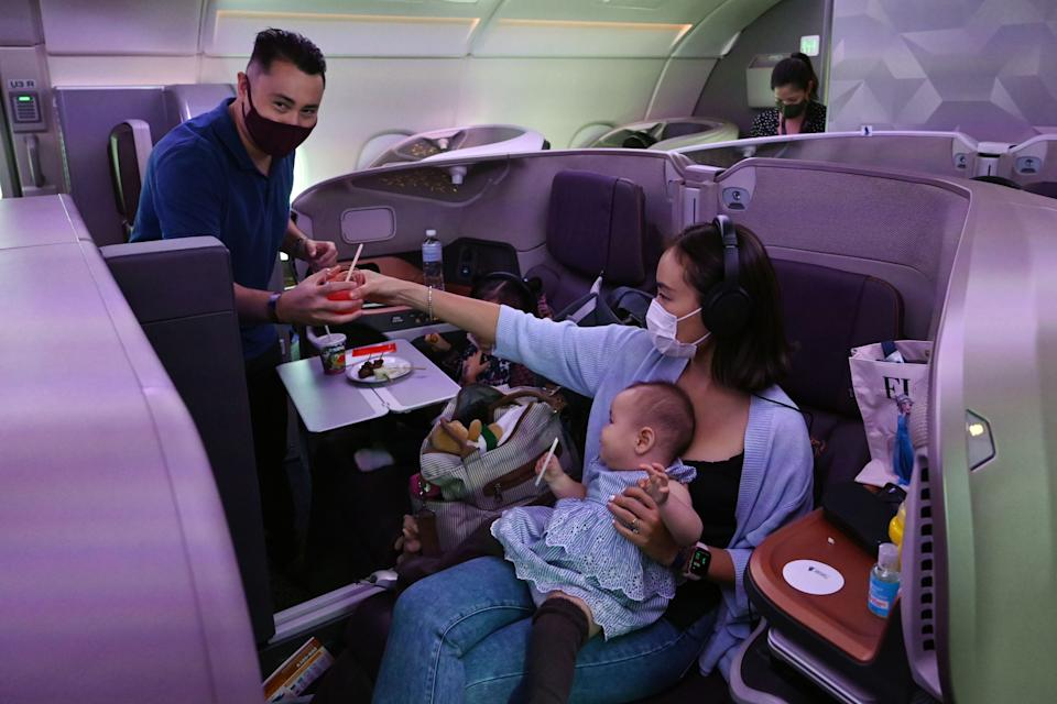 A couple and their children dine in business class during the inaugural lunch at Restaurant A380 @Changi onboard a Singapore Airlines Airbus A380 plane at Changi International Airport in Singapore on October 24, 2020. (Photo by ROSLAN RAHMAN / AFP) (Photo by ROSLAN RAHMAN/AFP via Getty Images)