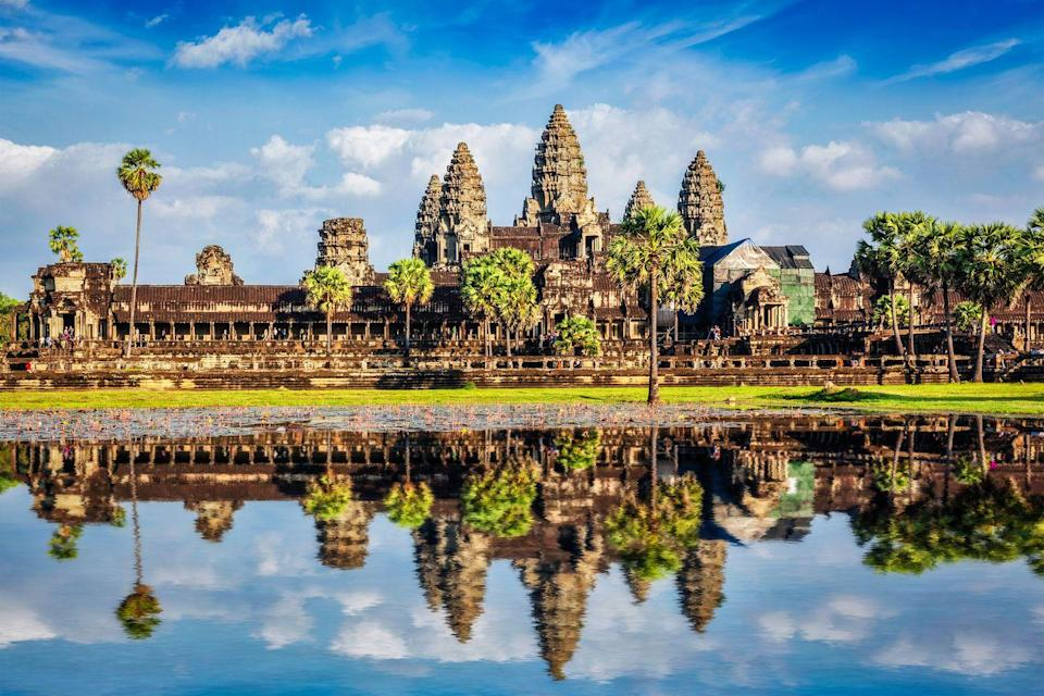 "<p>The historic stone capital of <a href=""https://whc.unesco.org/en/list/668/"" rel=""nofollow noopener"" target=""_blank"" data-ylk=""slk:Angkor Wat"" class=""link rapid-noclick-resp"">Angkor Wat</a> served as the center of the Khmer Empire from the 9th to 15th centuries. The towering temples acts as earthly representations of Mount Meru of the Hindu faith, where the ancient gods lived. According to inscriptions found in the city, it took nearly 300,000 workers and 6,000 elephants to create the immaculate example of classical Khmer style; although, it's believed the project was never fully finished. </p><p>The sprawling complex was transformed into a Buddhist temple in the 14th century, with statues and paintings of Buddha placed throughout. Over the years, Angkor Wat has seen much damage from weather and war, but archaeologists are working to restore the spiritual destination to its original glory.<br></p>"