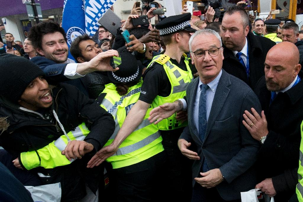 Leicester City manager Claudio Ranieri is mobbed by fans as he leaves an Italian restaurant in Leicester on May 3, 2016 (AFP Photo/Justin Tallis)