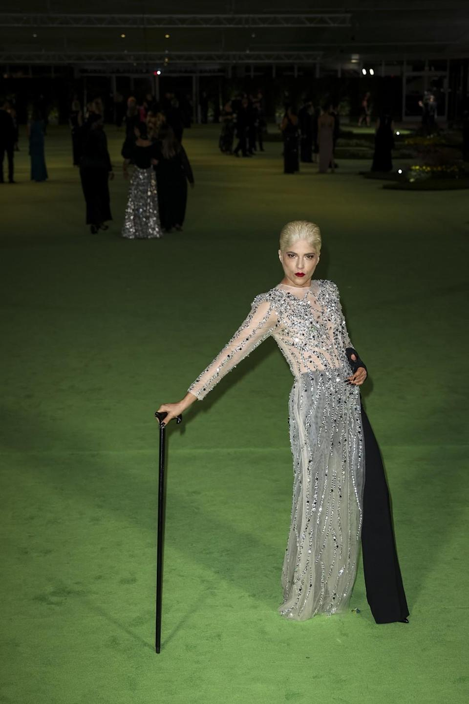 A woman in a silver dress and black pants posing with a cane on a green carpet