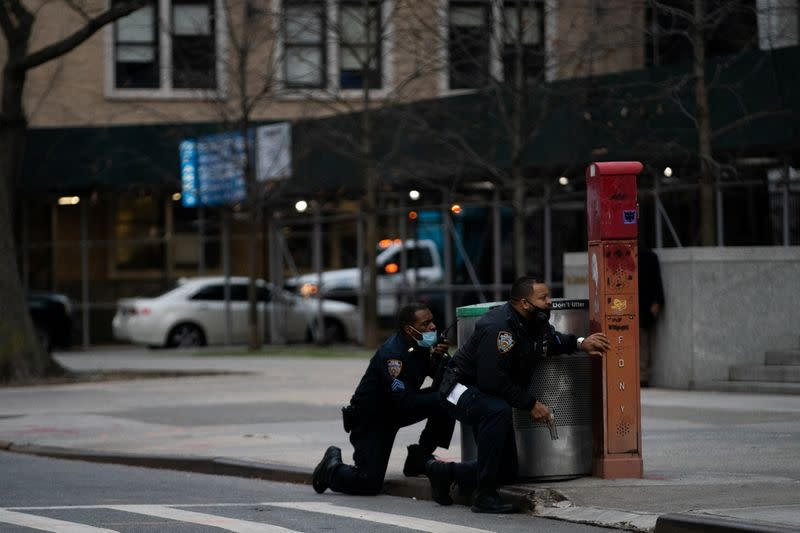 Police officers guard while a man is shooting outside the Cathedral Church of St. John the Divine in Manhattan