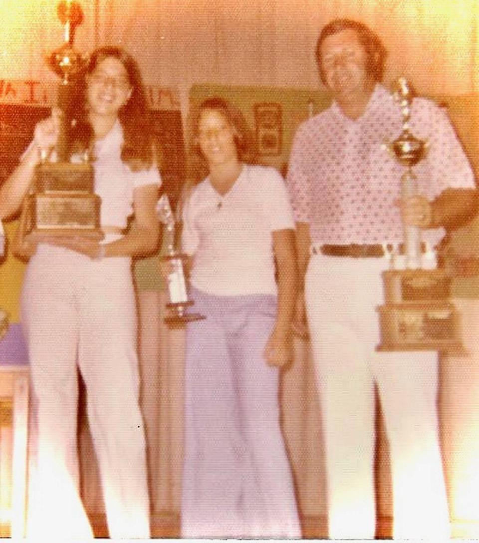 Diana Hernandez, middle, is in sixth grade at Leroy D. Fienberg Elementary School in Miami Beach in the 1970s when she receives an award from PE teacher Arnie Notkin, along with her sister Silvia. Notkin and his wife Myriam were among those missing Thursday after the Surfside condo tower collapsed.