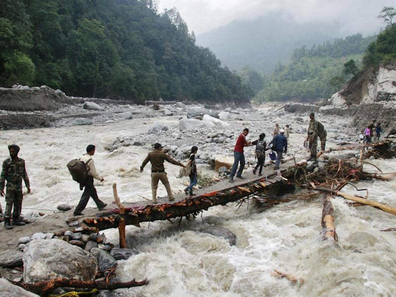 Indian army personnel help stranded people cross a flooded river after heavy rains in the Himalayan state of Uttarakhand, Flash floods and landslides killed thousands. (Reuters)