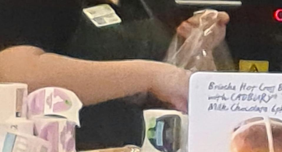Bakery worker's hands shown handling a bag with no gloves.